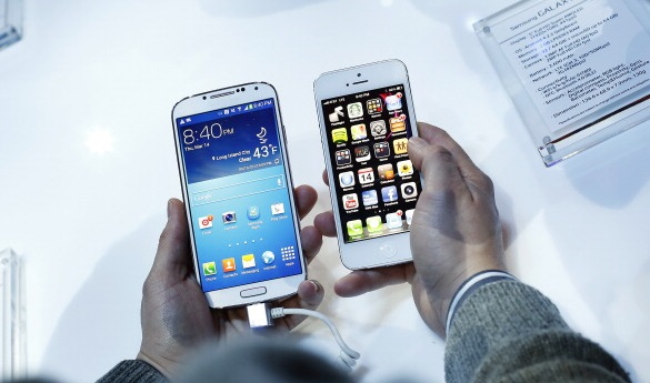 An attendee holds a Samsung Electronics Co. Galaxy S4 smartphone, left, next to an Apple Inc. iPhone 5 during an event at Radio City Music Hall in New York, U.S., on Thursday, March 14, 2013. Samsung unveiled the Galaxy S4 with a bigger screen and software that tracks eye movements as the world's biggest smartphone seller takes its battle with Apple Inc. to the iPhone maker's home market. Photographer: Victor J. Blue/Bloomberg via Getty Images