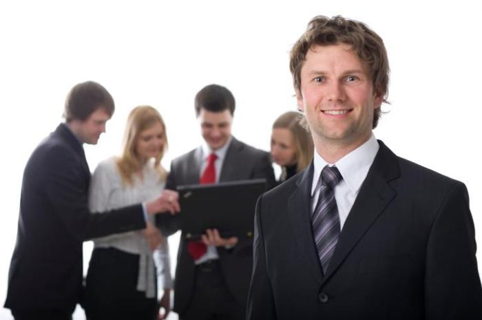 Smiling business man with colleagues in the background