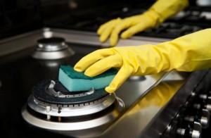 Mãos com luva de latex limpando fogão industrial