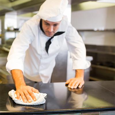Chefe de cozinha limpando superfície da cozinha
